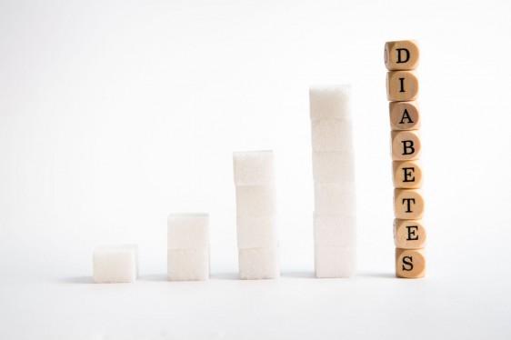 terrones de azúcar acomodados como grpafica de barras en crecimiento cubos de madera con la palabra diabetes son la columna mas grande