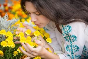 Una mujer oliendo flores
