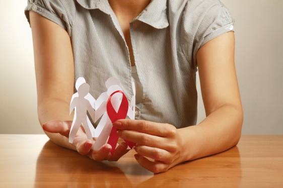 Mujer sostiene en sus manos recorte de papel con forma de personas y un listón rojo del SIDA