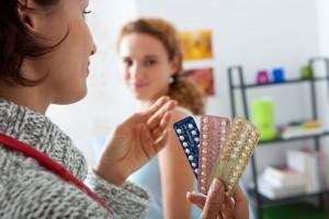 Mujer sosteniendo métodos anticonceptivos en la mano al fondo una adolescente