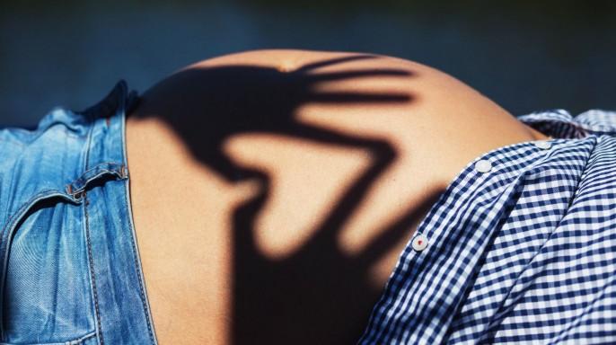 Acercamiento al estomago de mujer embarazada en donde se proyecta una sombra de dos manos que forma un corazón