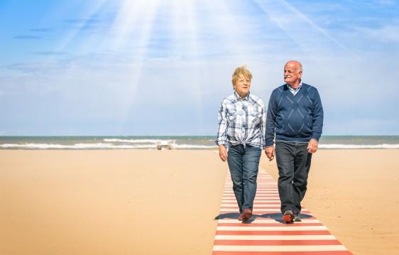 Adultos mayores caminando en una playa