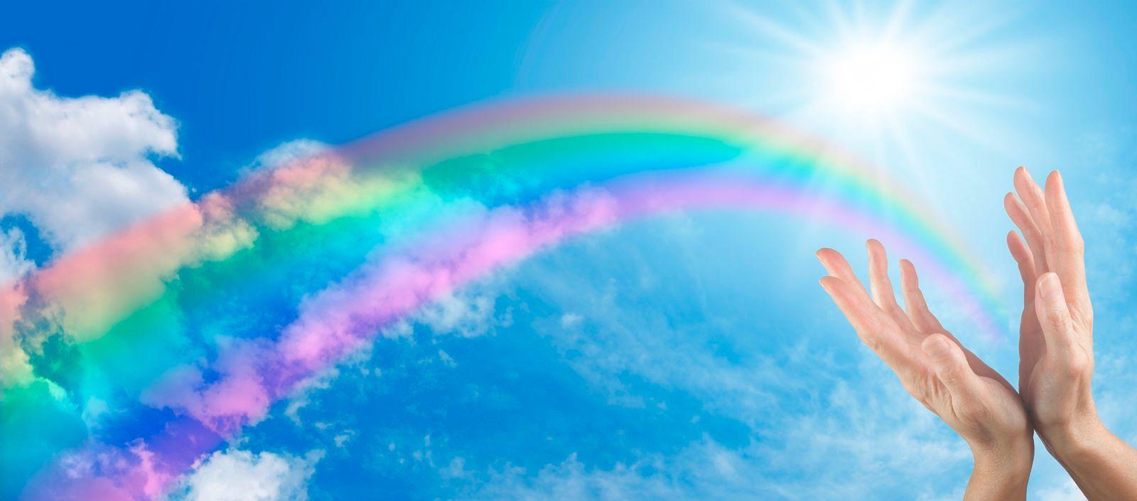 Manos abiertas hacia el cielo con un arco iris en el fondo