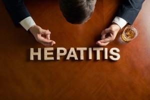 Persona sentada en una mesa con letras que forma la palabra HEPATITIS