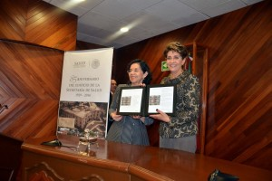 Patricia Cravioto Galindo y Mercedes Juan sosteniendo en sus manos la Estampilla postal conmemorativa al 85 Aniversario del Edificio de la Secretaría de Salud