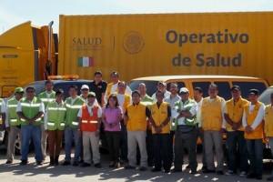 Al frente equipo de 25 personas al fondo dos camionetas y un trailer amarillos