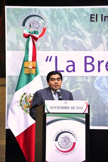 Miguel Barbosa Huerta de pie en un podium con un microfono