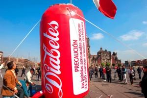 """Globo rojo de cinco metros de altura conletras blancas manuscritas con la palabra """"Diabetes"""" en el zócalo de la ciudad de M+exico al fondo la bandera de los Estados Unidos Mexicanos"""
