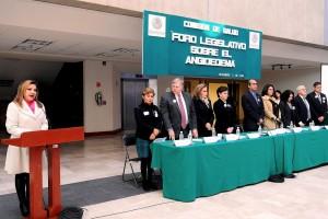 """Grupo de funcionarios de pie al fondo letrero """"foro legislativo Angioedema Hereditario"""""""