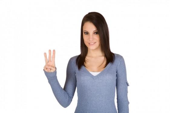 Mujer mostrando tres dedos de la mano derecha