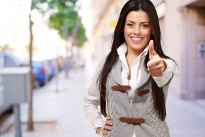 Mujer haciendo señal de aprovación en una calle