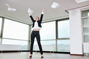 Mujer aventando papeles al aire en una oficina