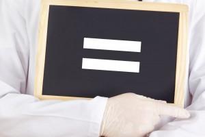 Un médico sostiene un letrero con el signo de igual pintado