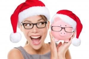 Mujer con gorro de navidad y una alcancía en forma de puerquito con sombrero navideño