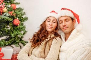 Pareja abrazándose al lado de un arbol de navidad