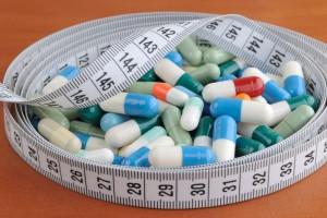 Medicamentos en píldoras rodeados por una cinta metrica