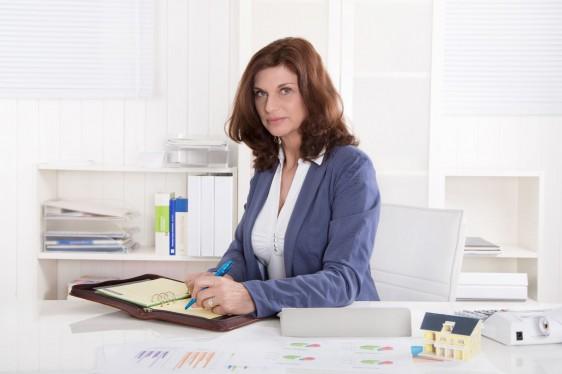 Mujer escribiendo en una libreta sentada en una mesa
