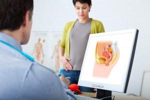 Un ginecólogo observando una ilustración a la izquierda con una mujer de pie