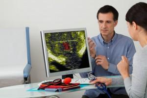 Hombre en una consulta observando con doctora una ecografía