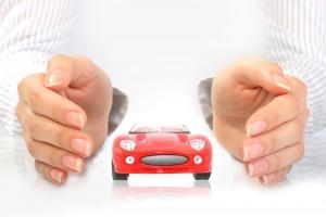 Mujer protegiendo con sus manos un coche rojo