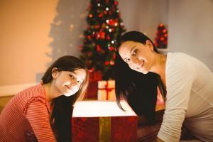 Madre e hijas sentadas al lado de un árbol de navidad y un regalo abierto