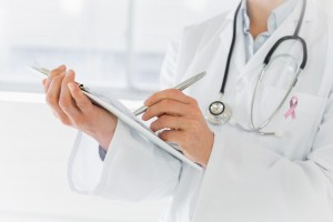 Acercamiento a una doctora que sostiene una tabla con clip escribiendo