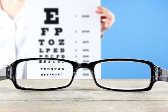 Lentes en una mesa, al fondo pruebas de letras para evaluar visión