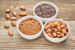 Cacao en recipiente de cerámica blanco en grano, polvo y semillas