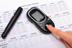 Mano de mujer en un glucómetro abajo una hoja de reporte de glucosa