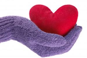 Acercamiento a una mano con guante morado que sostiene un corazón de peluche