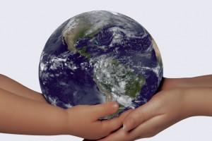 Portada de la Actualización de 2014, Eliminación de la transmisión maternoinfantil del VIH y la sífilis en la Región de las Américas las manos de un niño reciben una esfera con la imagen del mundo de las manos de una mujer