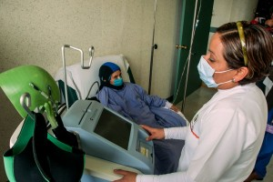 Especialista operando equipo y paciente sentada con Dignicap en su cabeza
