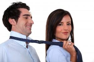 Mujer agarrando de la corbata a un hombre