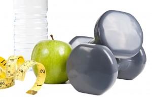 Agua, manzana y pesas con una cinta metrica