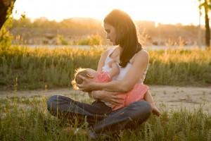 Madre amamantando a un bebé en un atardecer en el campo