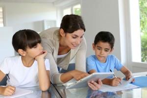 Maestra con dos niños en un salón de clases