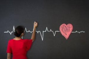 Adolescente dibujando en un pizarrón un electrocardiograma