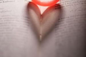 Condón que proyecta una sombra en forma de corazón en un libro