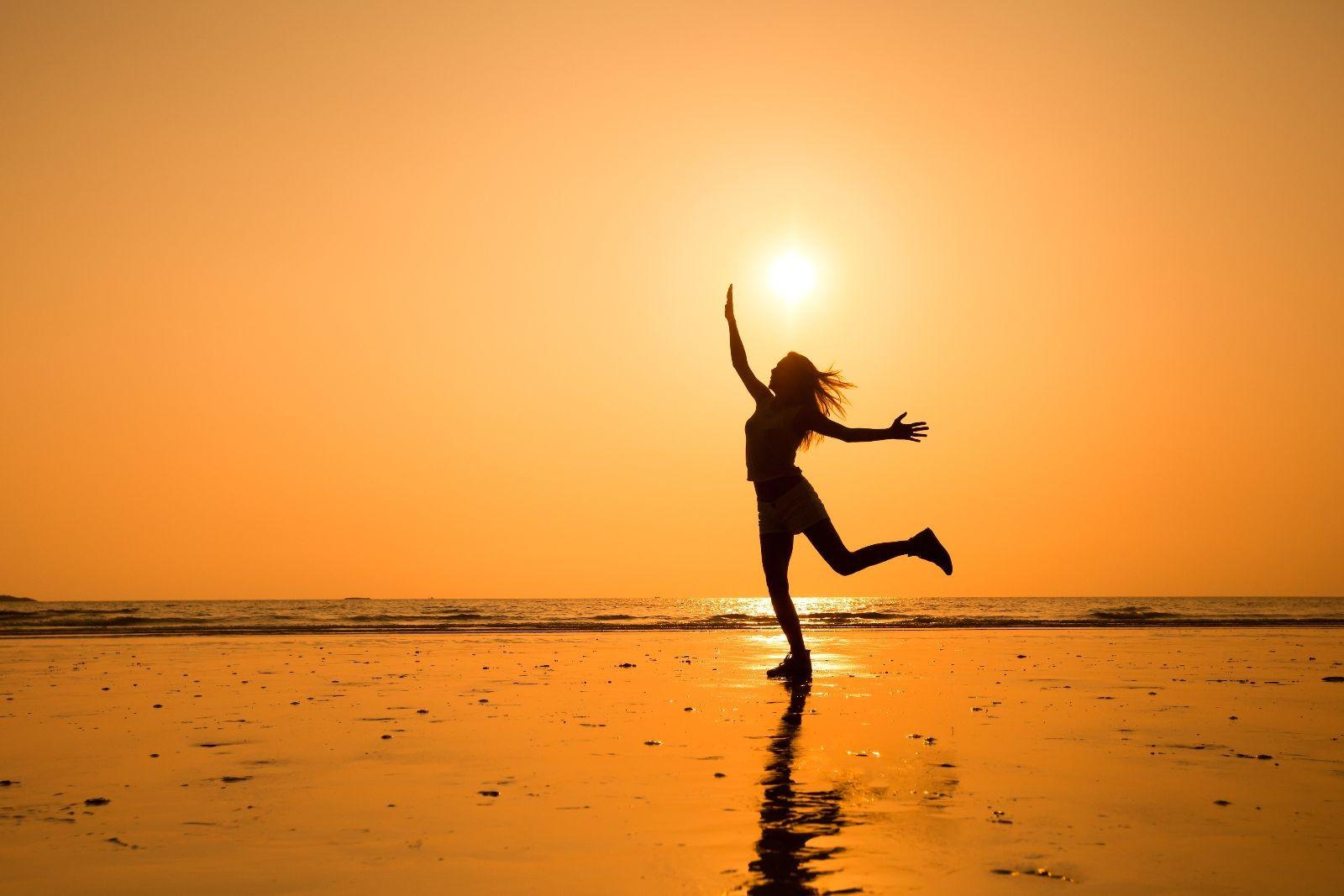 Silueta de una niña en una playa con un atardecer naranja