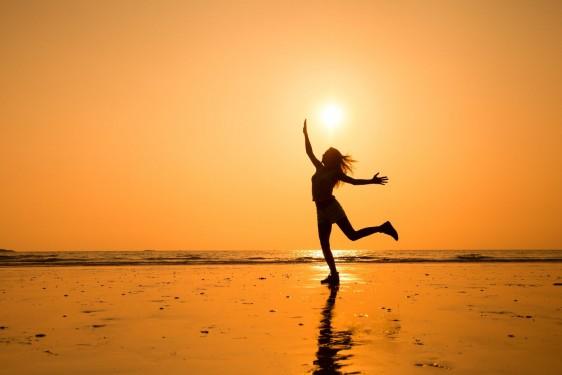 Silueta de una miña en una playa con un atardecer naranja