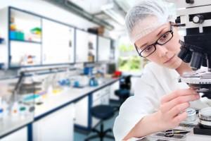 Mujer revisando microscopio en un laboratorio