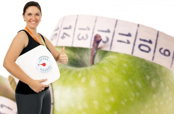 Mujer sosteniendo una bascula al fondo una manzana con cinta métrica