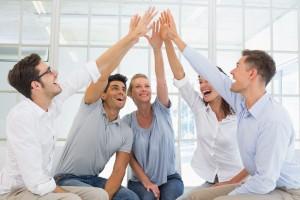 Grupo de personas sentadas con la mano en alto tocandose