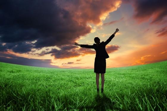 Mujer con los brazos abiertos en un atardecer en el campo