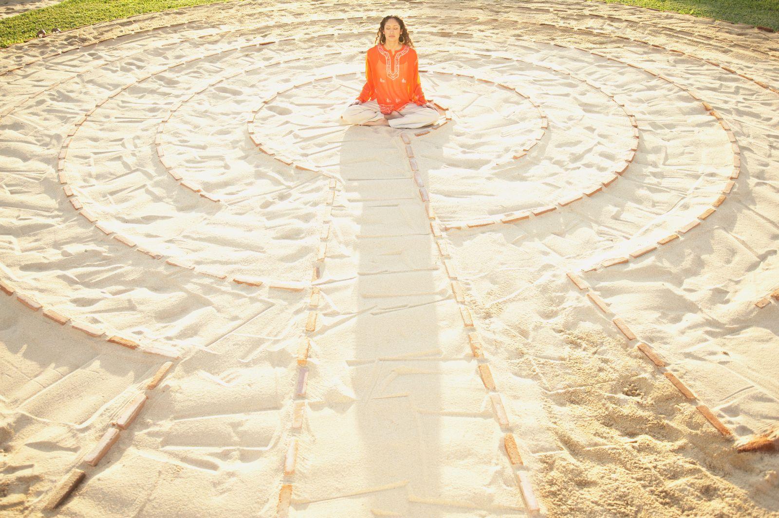 Mujer sentada en medio de en un laberinto ibujado en la arena