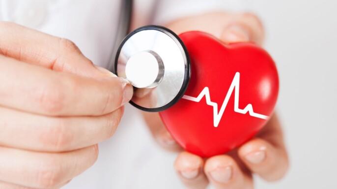 Acercamiento a las manos de un doctor que sostiene estetoscopio y corazón rojo con electrocardiograma
