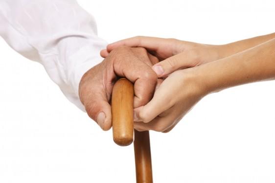 Acercamiento a las manos de un adulto mayor steniendo un bastón cin la mano de una mujer agarrándole la mano
