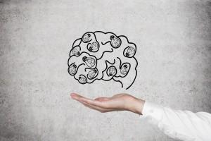 Ilustración de un cerebro con la mano de una persona sosteniendolo