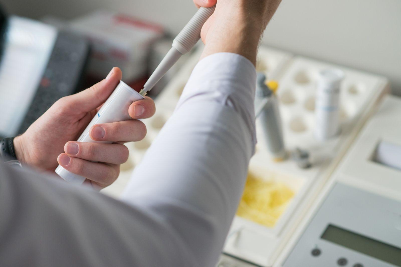 Acercamiento a las manos de una investigadora en un laboratorio