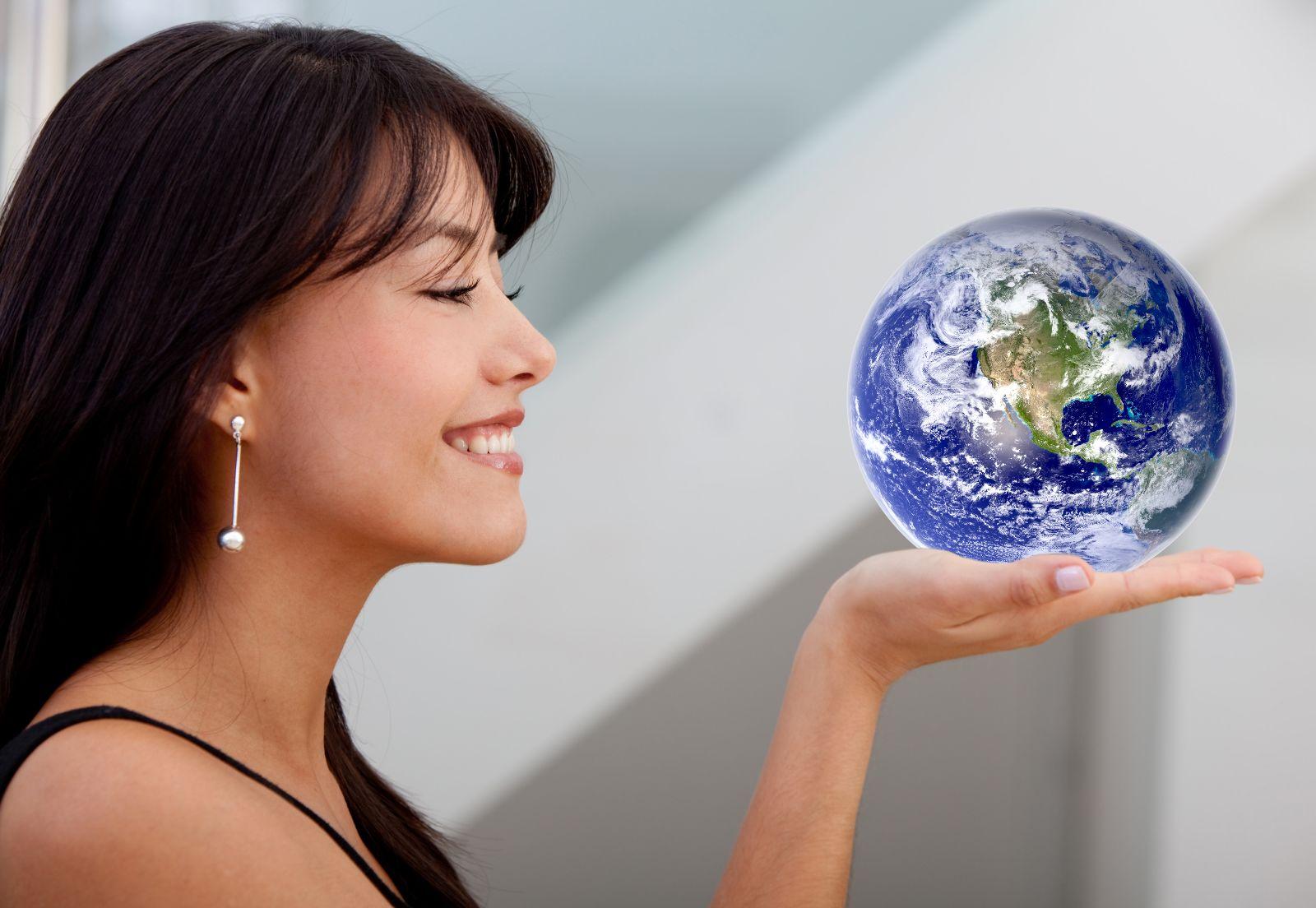 Mujer ejecutiva sonriendo y sosteniendo un mundo en su manos